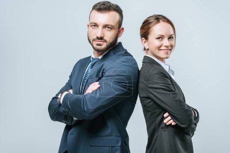 Photo for Smiling businesswoman and businessman standing with crossed arms and looking at camera isolated on grey - Royalty Free Image