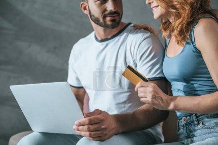 Photo pour Cropped image du couple shopping en ligne avec ordinateur portable et de carte de crédit à la maison - image libre de droit