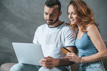 Photo pour Couple heureux magasinage en ligne avec ordinateur portable et de carte de crédit à la maison - image libre de droit