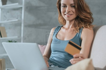 smiling woman shopping online with laptop and credit card at home
