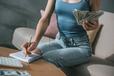 cropped image of woman planning budget at home, holding dollars and writing something to notebook
