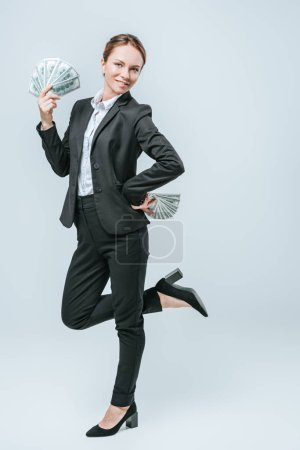 happy attractive financier posing with dollar banknotes isolated on grey
