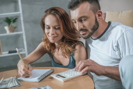 couple planning family budget with notebook and calculator in living room