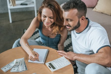 couple planning family budget and writing something to notebook in living room
