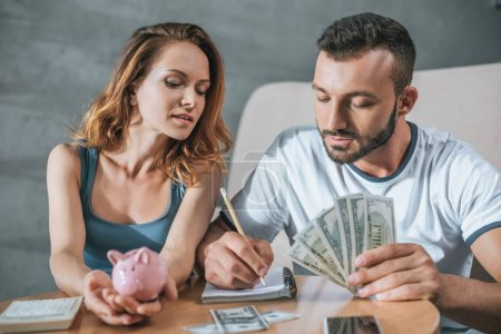 couple planning family budget with piggy bank and dollars in living room