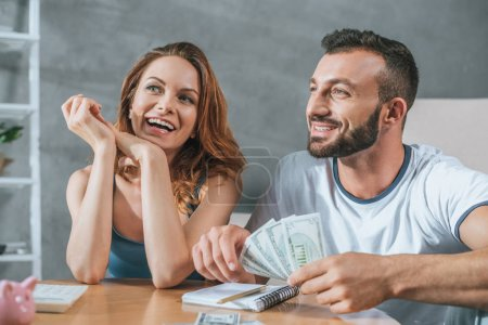 smiling couple planning family budget and looking away in living room