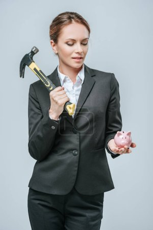 attractive financier holding hammer and piggy bank isolated on grey
