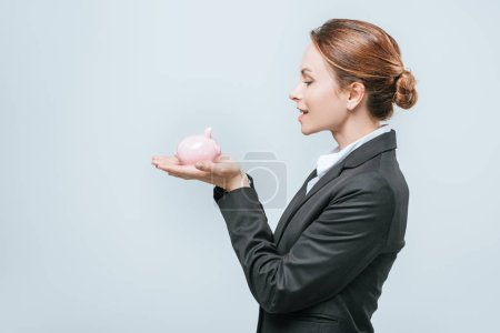 side view of attractive financier holding piggy bank isolated on grey