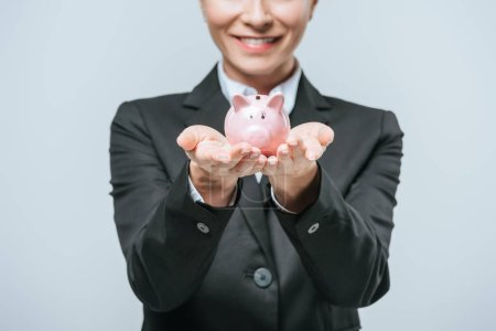 cropped image of smiling financier holding piggy bank isolated on grey