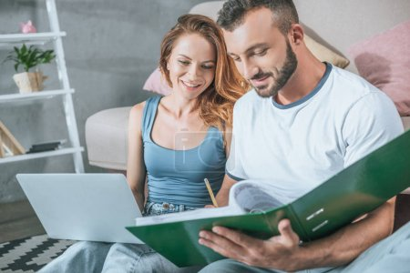 happy couple planning family budget in living room with laptop and folder