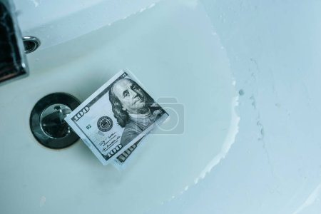 top view of dollar banknote in water in sink