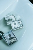 top view of dollar banknotes in water in sink