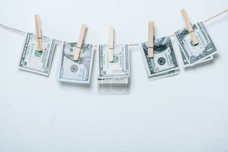 dollar banknotes hanging on rope isolated on grey