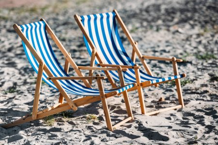striped beach chairs and cooler on sandy coast