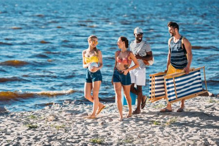 smiling young multiethnic friends with beach items walking on sandy sea coast