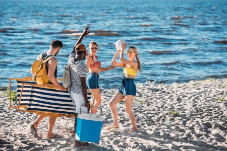 happy young multiethnic friends with beach items smiling each other on sandy sea coast