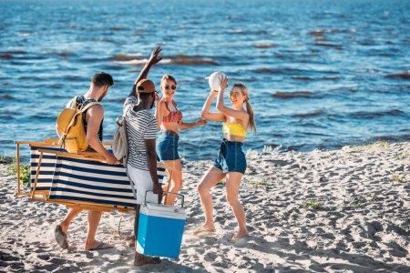 Photo pour Heureux jeunes amis multiethniques avec des Articles de plage souriant mutuellement sur la côte de la mer de sable - image libre de droit