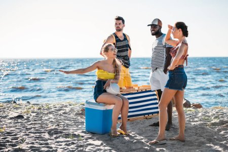 happy young multiethnic friends with beach items spending time on sandy sea coast