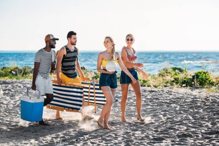 happy young multiethnic friends with beach chairs, cooler and ball walking on sandy beach