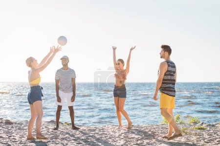 happy young multiethnic friends playing beach volleyball at sea coast