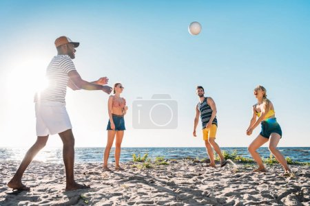 Photo for Happy young multiethnic friends playing volleyball on sandy beach - Royalty Free Image