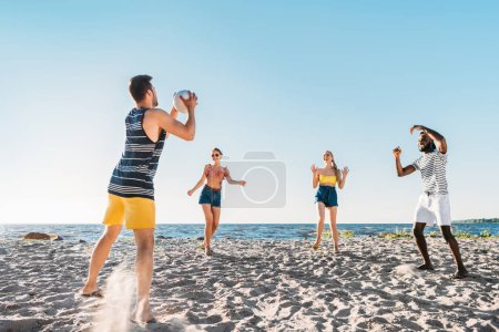 happy young multiethnic friends playing beach volleyball