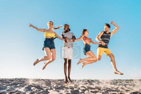 glückliche junge multiethnische Freunde halten Händchen und springen in Sandstrand