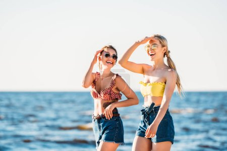 Photo for Happy young women in sunglasses walking together on beach - Royalty Free Image
