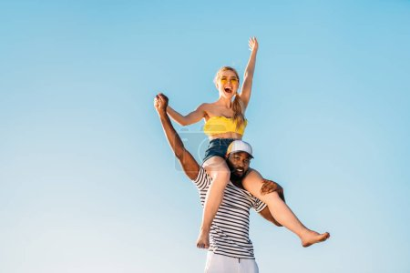 low angle view of happy young multiethnic couple having fun together against blue sky