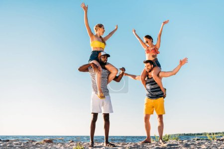 cheerful young multiethnic friends having fun together on sandy beach