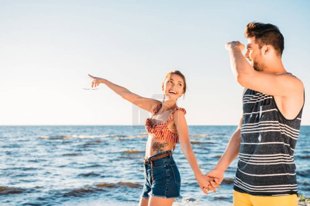 Photo for Happy young couple holding hands and looking away while walking together on beach - Royalty Free Image
