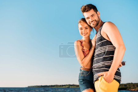 beautiful happy young couple smiling at camera while standing together on beach