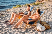 high angle view of happy young couple resting on chaise lounges on sandy beach
