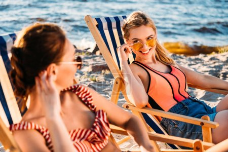 beautiful young women smiling each other while sitting in chaise lounges on sandy beach