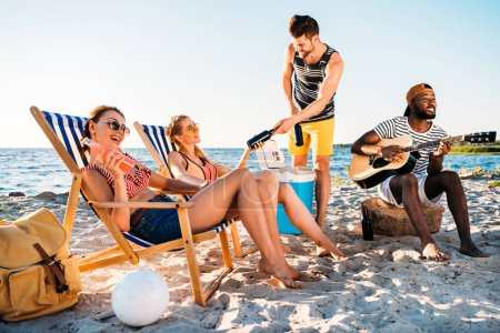 happy young multiethnic friends with guitar and drinks spending time together on sandy beach