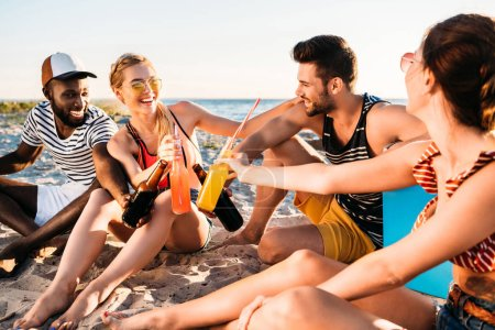 happy young multiethnic friends clinking glass bottles with drinks while sitting on sandy beach