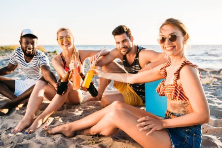 happy young multiethnic friends holding glass bottles with drinks and smiling at camera on sandy beach