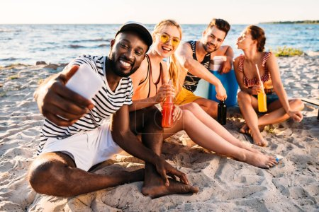 happy young multiethnic friends taking selfie with smartphone while spending time together on sandy beach
