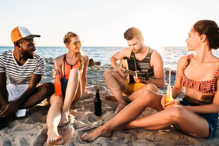 happy young multiethnic friends with drinks and guitar sitting on sandy beach