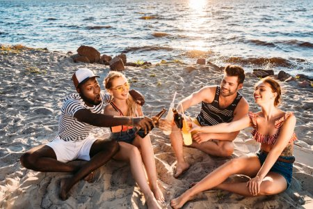 high angle view of happy young multiethnic friends clinking glass bottles with drinks on sandy beach at sunset