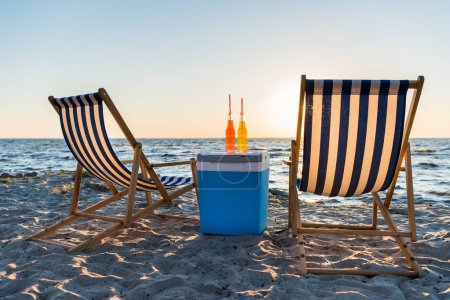Photo for Refreshing beverages on cooler and chaise lounges on sandy beach at sunset - Royalty Free Image