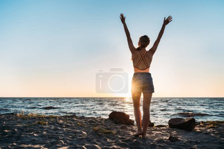 back view of young woman raising hands while standing on sandy beach at sunset