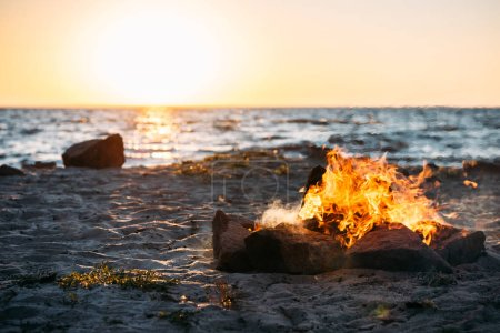 Photo for Bonfire on sandy sea coast at majestic sunset - Royalty Free Image
