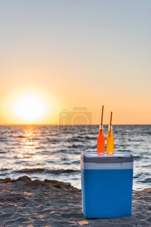 glass bottles with summer beverages and straws on cooler at sandy beach at sunset