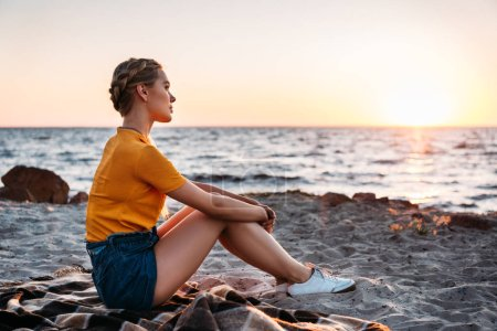 side view of pensive young woman sitting on plaid at beautiful sea coast at sunset