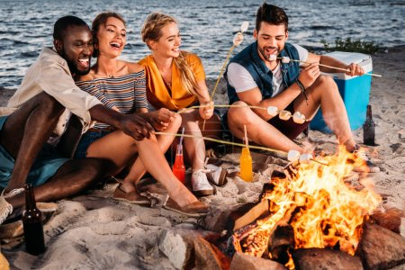 happy young multiethnic friends roasting marshmallows at bonfire on beach at sunset