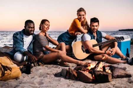 happy young multiethnic friends with guitar looking at bonfire while sitting together on sandy beach