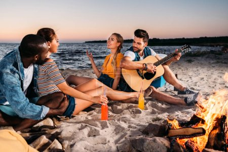 happy young multiethnic friends enjoying guitar and spending time together on sandy beach at sunset