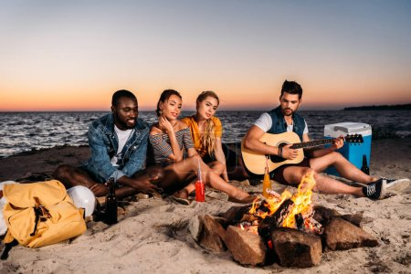 young multiethnic friends enjoying guitar and spending time together on sandy beach at sunset
