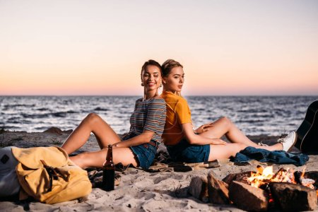 happy young women sitting back to back on sandy beach at sunset